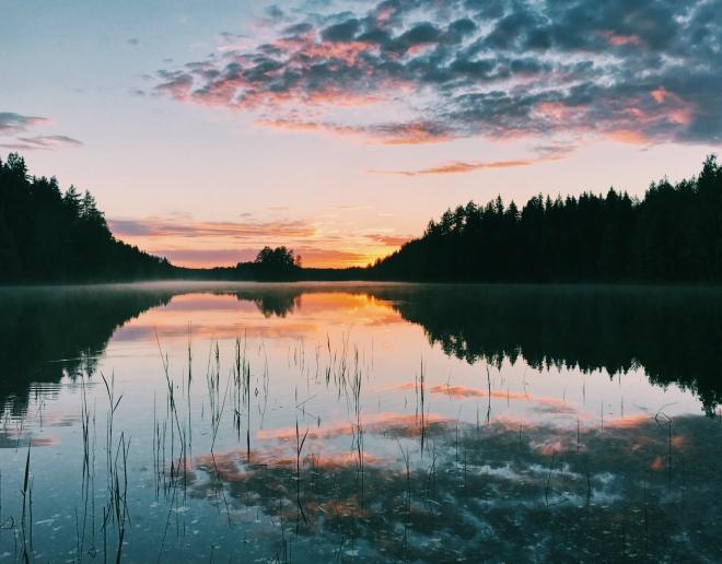 The midnight sun of Finland, peeking over a lake.